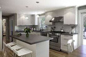 pretty gray kitchen cabinets with kitchen sink and stainless steel appliances with white bar stools and small kitchen island with slate countertops and