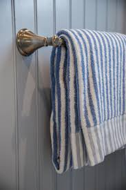 guest bathroom towels: classic and timeless a champagne bronze towel bar coordinates with surrounding hardware and capably holds nautical inspired blue and white striped bath