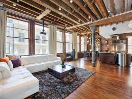 Open sitting and dining areas with requisite exposed joists and brick in  this loft on Prince