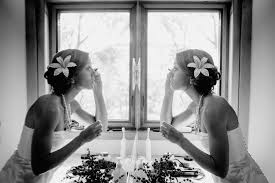 mirror reflection different. bride putting on makeup reflection mirror symmetry different