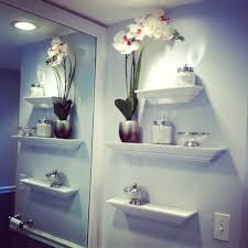 modern rack wall bathroom decoration white flowers on vase some jars glass bowl white open rack big mirror white wall colored