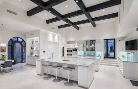 luxury contemporary kitchen with two islands carrara marble counters and wood beam ceiling