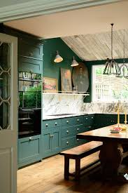 deep dark green cabinets and walls original wooden floorboards