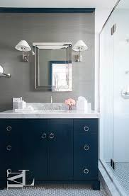 Navy blue and gray bathroom features walls clad in grey grasscloth lined  with a polished nickel framed medicine cabinet illuminated by polished  nickel ...