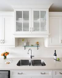 glass doors shelf above kitchen sink create a soft light feeling in this small kitchen