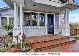 entrance porch with brick tile floor and black door