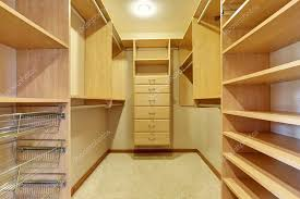 large walk in closet with hardwood floor also including many shelves fotos de stock