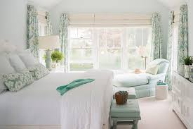 white and blue bedroom features an off white headboard on bed dressed in white and turquoise blue hotel bedding aqua ikat pillows and an aqua throw blanket
