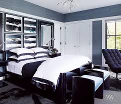 Contemporary blue bedroom features walls clad in blue grasscloth lined with  black and white abstract art
