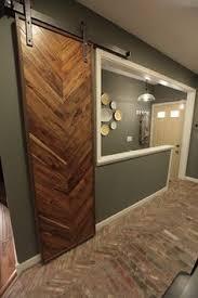 a herringbone pattern of interior brick veneer used as brick floor tile in this kitchen entryway