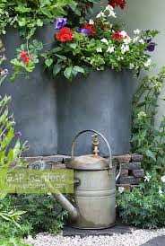 metal watering can next to lead planters with red white and blue summer bedding plants entente cordiale a touch of france garden sponsored by bonne