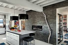 modern kitchen wall fireplace black oversized pendant lights gray island with white countertop backless bar stools book shelves exposed ceiling beams