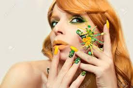 緑黄色鮮やかな流行メイクや別の形と色と灰色の背景に赤い髪の少女の輝き
