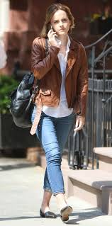 picture of black flats cropped blue jeans a white shirt a brown leather jacket and a black backpack