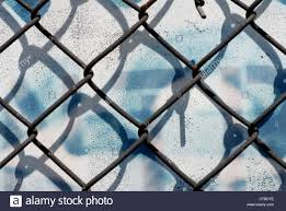 close up on a chain link fence against a white background with blue dripping spray paint