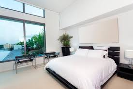 white bedroom with dark furniture. sparsely furnished white bedroom with dark furniture elevated ceiling windows flood the room m