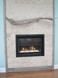 interior grey stone fireplace having carved grey wooden fireplace mantels and black metal firebox on