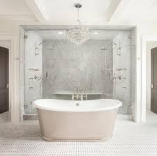 stunning bathroom boasts a robert abbey bling chandelier hanging over a freestanding tub and a floor mount tub filler atop a marble basket weave floor