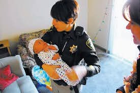 Officer Lourdes Smith holds the 3 week-old boy whose family Smith and Sgt.  Richard Meyers helped in November. (Courtesy Las Vegas Metro PD) | Las  Vegas Review-Journal