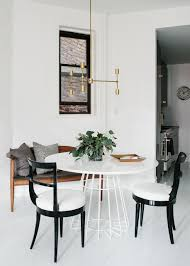 gorgeous scandinavian dining room e with white shiplap floors a wooden bench decorted with velvet throw pillows a gold geometric pendant light
