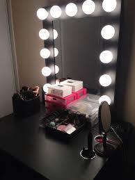 black wooden makeup vanity set with lighted mirror in the corner