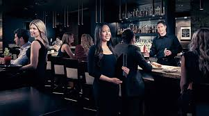 home the keg steakhouse bar employment a female keg server male bartender and female host smile and look at the camera