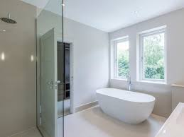 white tub luxurious bathroom with freestanding tub tower faucet and placed by a window