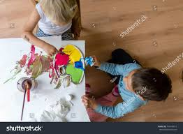 high angle view of two brothers painting with colorful paints