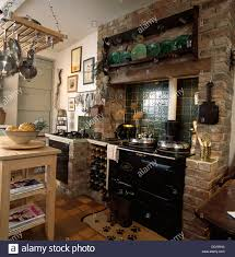 Kitchen Pan Storage Wine Storage Rack Beside Black Aga In Exposed Brick Fireplace
