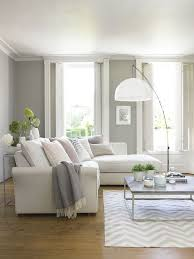 A medium sized living room furnished with a three-seat sofa combination in  plain gray