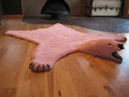 light red faux bear skin rug with head and claw on laminate hickory wood flooring