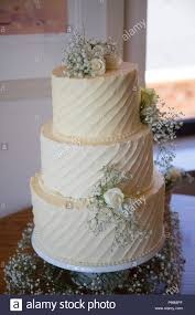 Three Tiered Wedding Cake Covered In Buttercream Icing And Real