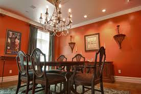 brilliant dining room design with luxury chandelier and orange wall color also dark grey curtain and also wooden dining furniture idea