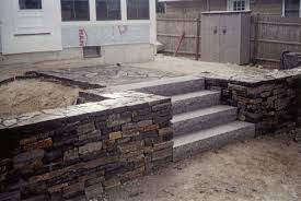 granite steps and stacked stone walls welcomes visitors to this maine home stone retaining