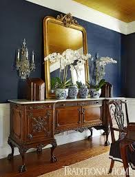 dining room mirrors antique. an antique server in the dining room matches classic look of table and chairs. a large mirror above reflects mirrors n