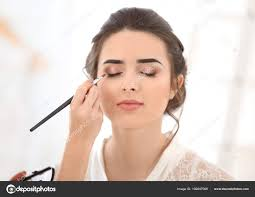 professional makeup artist working young woman salon stock photo