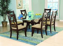 dining room oval glass room table white pattern fur rug beige wooden chairs teak armoire
