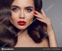 beauty makeup elegant woman portrait with red lipanicured nails healthy wavy hair style y brunette looking at camera over gray studio