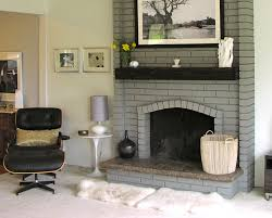painted brick fireplace in a light gray with dark wood mantel in a contemporary setting
