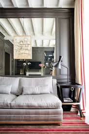 marquis faubourg saint honoré hotel room designed by michele bonan is warmed by a striped grey and red rug mirrored wall illusion of e
