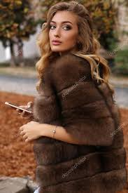 gorgeous sensual woman with blond hair in luxurious fur coat stock photo