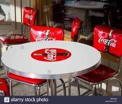 red coca cola chairs around a white coca cola table stock image