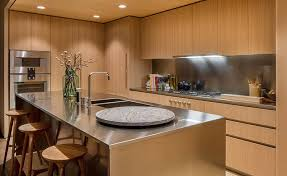 This modern kitchen features honey-hued American oak cabinets with  satin-finish stainless steel