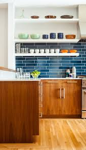 wooden cabinetries wooden flooring navy tile kitchen backsplash white wooden floating shelves bowls plates cups stainless steel stove