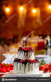 two level white wedding cake decorated with fresh red fruits and berries drenched in chocolate bright banquet table decoration on background of lights