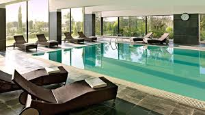 glass door ideas for luxury indoor swimming pool with comfortable lounge chairs