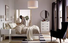 Woman standing in a bedroom with IKEA bed, armchair, mirror, drawers and rug