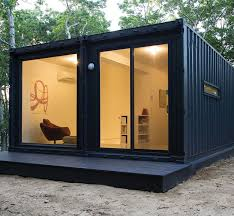 Outside view of an open-plan living room in midnight blue shipping container  with glass