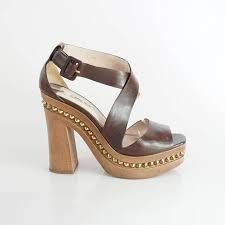 these miu miu heels have a strappy brown leather design there is a wooden platform