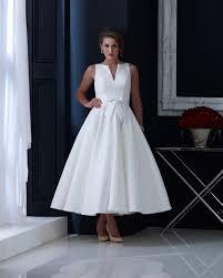 brocade tea length wedding dress with subtle bow and elegant cut